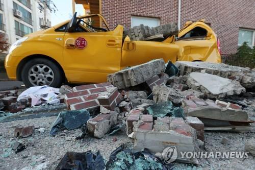 11月15日下午2时29分许,庆尚北道浦项市以北6公里处发生5.4级地震。图为浦项市北区兴海邑某幼儿园外墙坍塌,车辆严重毁损。图片来源:韩联社。