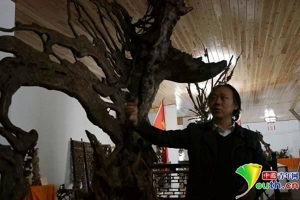 """""""巴渝工匠""""、根雕艺术家彭勇介绍自己的作品。张博 摄"""