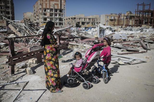 11月14日,在伊朗克尔曼沙阿省的萨尔波勒扎哈卜,一名妇女带着孩子站在倒塌建筑的废墟旁。(新华社发)