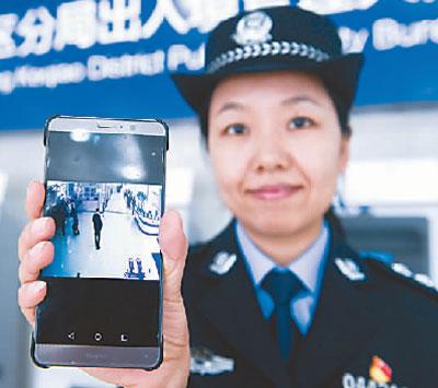 """浙江绍兴柯桥区公循分局收支境大厅的民警展示手机微信的实时""""视频大厅"""",可以实时检察办证大厅内的人流量,人们可通过这一功效合理摆设前往大厅管理营业的时间。新华社发"""