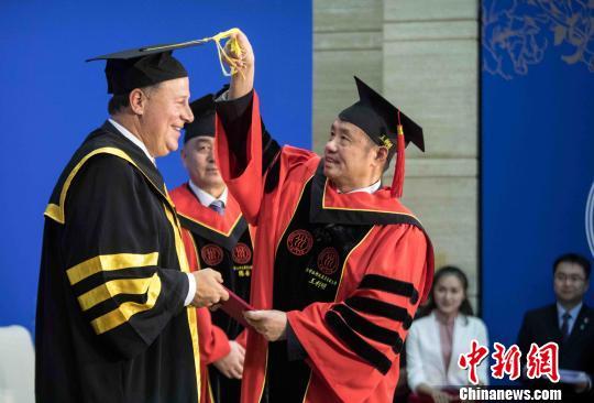 正在我国拜望的巴拿马总统巴雷拉11月18日获得我国百姓大学声誉博士学位。 王浩丞 摄