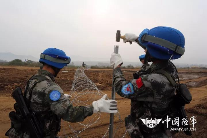 陆军第83集团军某合成旅步兵营在确山基地开展以武装分子发生交火为背景的维和营地安全防卫演练。图为修建维和营地防护铁丝网。