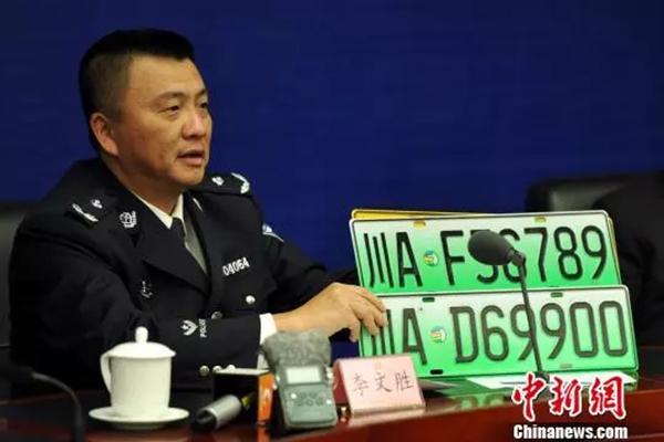 成都市公安局副局长、交管局局长李文胜展示新能源汽车专用号牌。 中新网 图