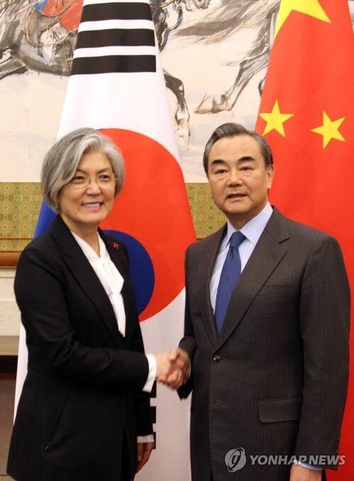 资料图:11月22日下午,在北京钓鱼台国宾馆,韩国外交部长官康京和(左)同中国外交部长王毅举行中韩外长会谈前握手。(韩联社)