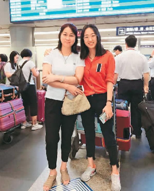 """穆赛(右一)与母亲在机场依依惜别。临行前父母还在嘱咐她:""""在国外一定要保护好自己。安全最重要!"""" 人民日报 图"""