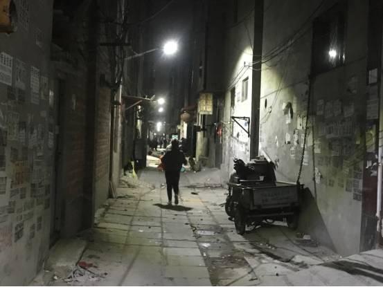 抱着枕头的女孩跑进巷子,准备渡过最后一晚。本报记者郝成摄影