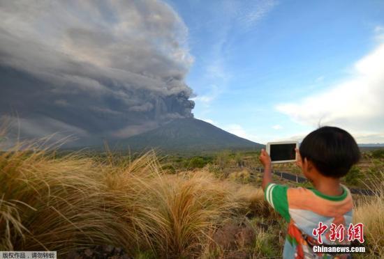 当地时间11月26日,印尼巴厘岛卡朗阿森,阿贡火山喷发。图为当地小朋友淡定拍照。