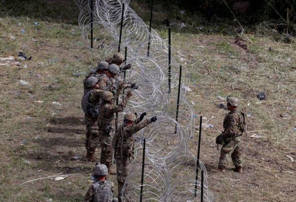 美军正在边境部署带有倒刺的铁丝网以阻挡非法移民。