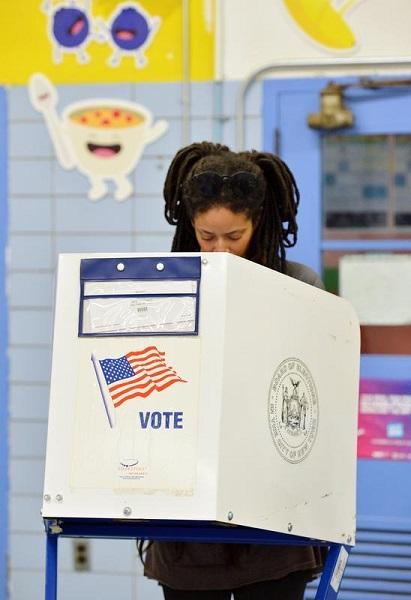 圖說:11月6日,在美國紐約曼哈頓,一名選民在一處投票站填寫選票。新華社