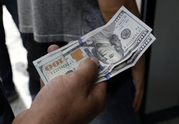资料图片:2018年8月10日,在土耳其首都安卡拉一处外币兑换店外,一名居民等待兑换手中的美元。新华社/美联