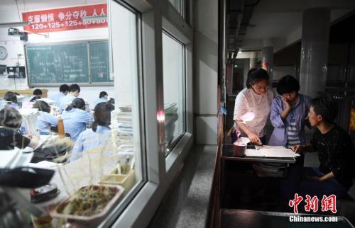 资料图:2018年5月23日晚,河北省邯郸市第一中学,高三学生在教室门口向老师问问题。 中新社发 郝群英 摄 图片来源:CNSPHOTO