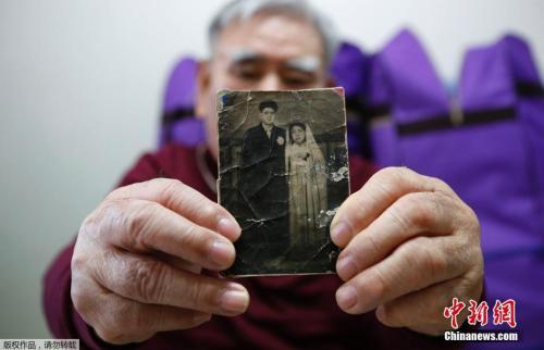 韩国老人Jang Choon在家中展示他在朝鲜的弟弟的照片。