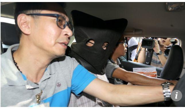 ▲警方逮捕许金山,为其戴上黑色头套。图据《南华早报》