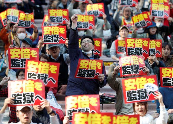 """25日,日本民众在东京集会,抗议安倍内阁篡改森友学园""""地价门""""相关文件,要求把安倍关进监狱。(路透社)"""