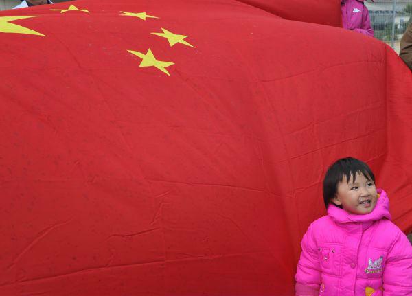 2011年2月28日,中國駐馬耳他大使館租用的第三艘用於撤離在利比亞中方人員的客輪抵達馬耳他首都瓦萊塔港後,一名使館工作人員的孩子站在迎接同胞的國旗前。(新華社)