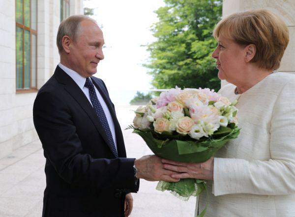 普京(左)18日在索契欢迎来访的默克尔(路透社)