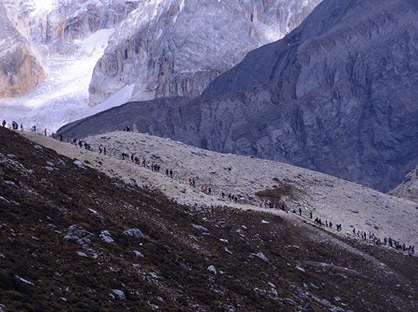 旅游高峰期,每天向景区海拔4600米以上景点攀登的游客绵延数公里。