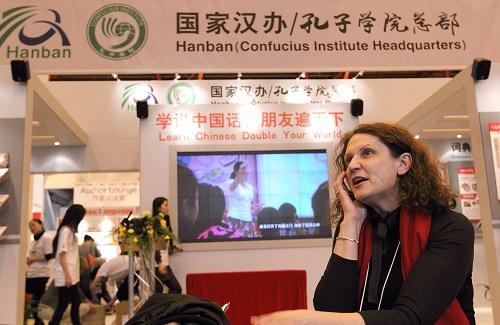 资料图片:2012年4月18日,在英国伦敦书展上,一名女子在中国国家汉办/孔子学院总部展台前打电话。新华社记者 殷刚 摄