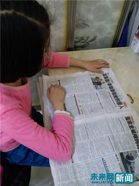 李明君的大女儿在报纸上看到了自己爸爸妈妈的救人事迹 受访者供图