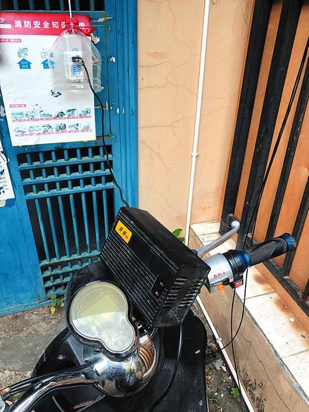 某小区居民从楼上私拉电线给电动自行车充电记者宋延康摄