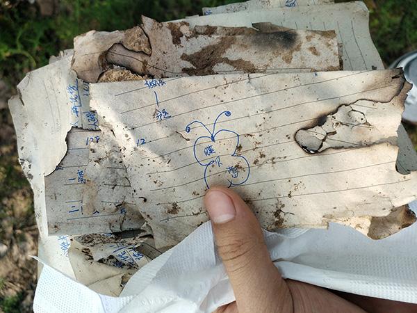 """2017年8月5日,天津,在距发现李文星遗体500米处的一个露天传销窝点,写有""""蝶贝蕾""""字样的笔记散落在地上。视觉中国 资料图"""