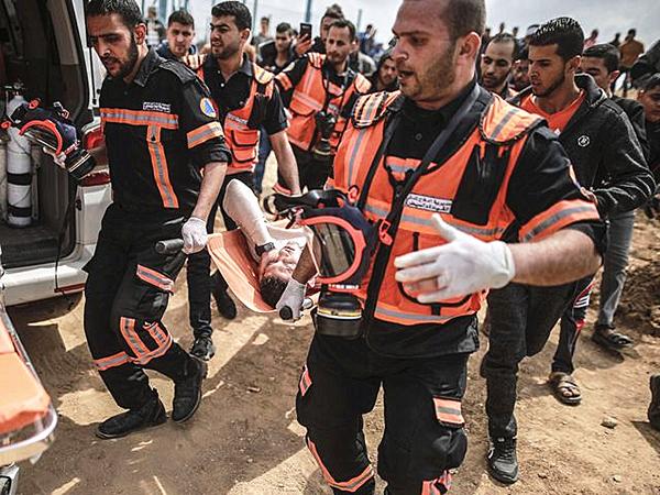 3月30日,加沙城,救援人员将一名受伤巴勒斯坦人抬向救护车。 新华社 图