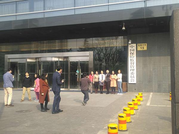 3月21日下午,更换门牌在即,保监会门口众多工作人员拍照留念。 杨峰 摄