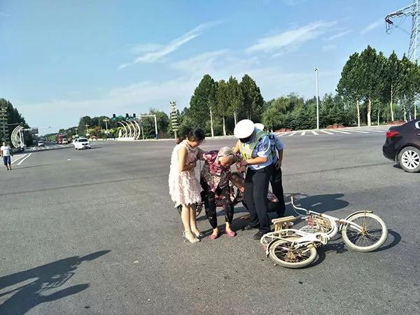 民警和女子一同扶起老人。 魏县交警大队宣传科 供图