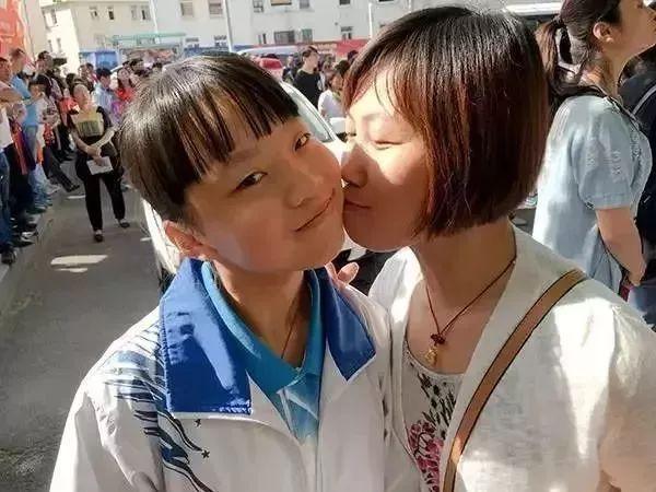 """""""第一天考完,妈妈在校门口亲了女儿一口。""""(图源:青岛日报)"""
