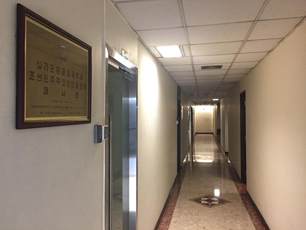 "</div> <div>&nbsp;</div> <div>  15-01,大使馆的门牌号和它在商务楼中的位置一样毫不起眼。</div> <p>  商务楼里空无一人的走道上,白色的灯光投射在紧闭的毛玻璃门上,不锈钢的门把手旁边,只见一把没有安装门铃按钮的密码锁。如果不是一块写着""朝鲜民主主义人民共和国驻新加坡共和国大使馆""的牌子挂在密码锁的上方,很难让人发现这是一处大使馆的所在地。</p> <p>  大使馆斜对面的15-09号,是一家朝鲜语(韩语)培训中心,一块写着""Speak Korean""的蓝底白字招牌显得非常醒目。</p> <p>  ""如果要进入朝鲜大使馆,必须通过电子邮件提前与使馆联系,只有获得准许后才有可能被接待。""在被问及朝鲜大使馆的具体信息时,在该楼保安处工作已超10年的印度裔安保人员阿格拉(化名)对澎湃新闻(www.thepaper.cn)说道。</p> <p>  阿格拉翻开了工作薄,随后又掏出手机搜索了5分多钟,终将搜集到的使馆信息展示给了记者。</p> <p>  阿格拉介绍所,在该栋楼里工作的朝鲜外交官员平时进出比较低调,很少与物管和保安处的人员打交道。即便自己在这栋楼做了10年保安,和朝鲜大使馆内的工作人员也并不熟络。</p> <p>  ""平日联系使馆的电话极少有人接听,即使是物业公司向朝鲜大使馆所在房间的业主征收水电费,也是通过电子邮件沟通。""阿格拉补充道,朝鲜大使馆房间平时也较安静,他们没有接到过其他住户的投诉。</p> <p>  在大楼内工作的另外两名人员面对记者询问,则表示根本没听说过楼里有朝鲜大使馆。</p> <p>  在一层告示处,澎湃新闻看到大楼内业主每一季度会有一次例行会议。阿格拉说,朝鲜大使馆的代表未曾出席过大楼例行会议;此外,一层还有整座大楼各房间的信箱,朝鲜使馆的信箱在一列信箱的最上方,且标注特殊。</p> <p></p> <div> <div class="