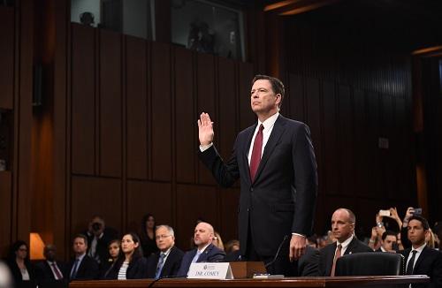 2017年6月8日,在美国华盛顿,美国联邦调查局(FBI)前局长詹姆斯·科米(前)在国会参议院出席听证会前宣誓。 新华社记者 殷博古 摄