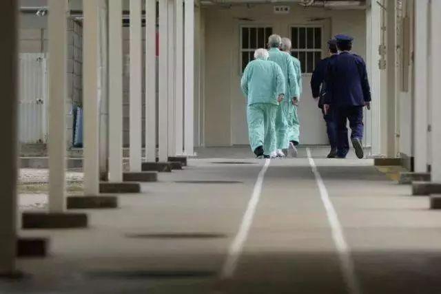 三名老年囚犯被獄警帶入佐世保監獄