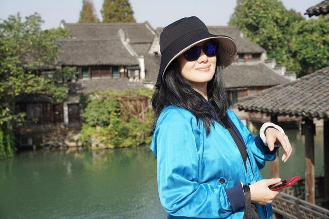咏梅穿蓝色外套配墨镜去旅游,戴上渔夫帽更减龄,49岁保养得真好