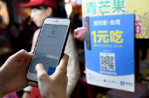 1月17日,一名顾客使用支付宝在台北宁夏夜市购买水果。(新华社)