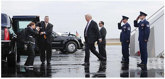 """白宫首席女摄影师克雷格海德(左一)为走下""""空军1号""""的特朗普拍照。"""