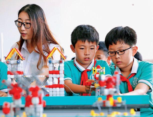 """6月7日,山东青岛通济实验学校的小学生学习""""机器人创意搭建与编程""""."""