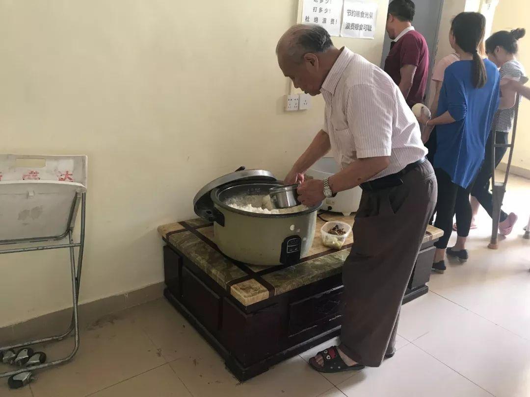 ▲胡厚培在打饭。新京报记者王佳慧摄