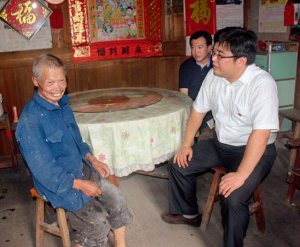 引进生李腾在贫困户家中走访慰问。秀屿新闻网 图