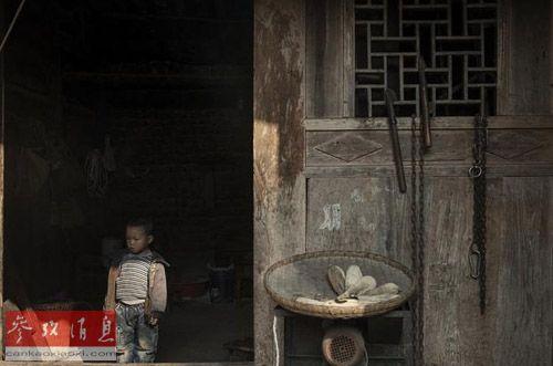 资料图片:贵州一名留守儿童孤单地站在家门口。