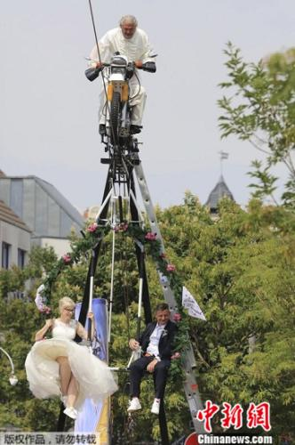 在德国东部Stassfurt小镇上,一对新人选择在一辆被钢索吊起的摩托车上,在离地约14米的空中,举办结婚仪式。