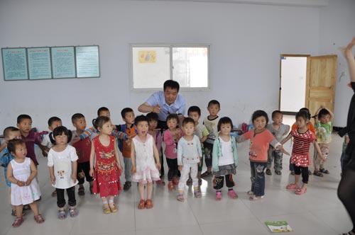 全国人大代表、河南省辉县市张村乡裴寨村党支部书记裴春亮和裴寨村幼儿园的孩子们在一起。 图片来源网络