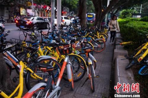 资料图:共享单车占用人行道,行人通过艰难。李南轩 摄