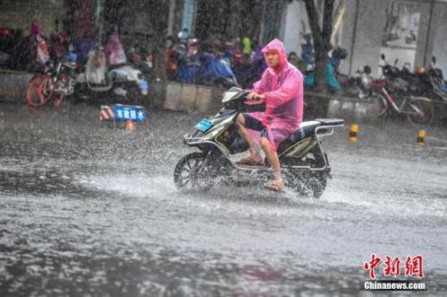 资料图:民众冒雨涉水出行。骆云飞 摄