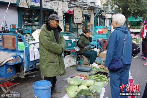 9月7日,黑龙江黑河,大早市上卖菜农民穿着棉衣和羽绒服。邱齐龙 摄 图片来源:视觉中国