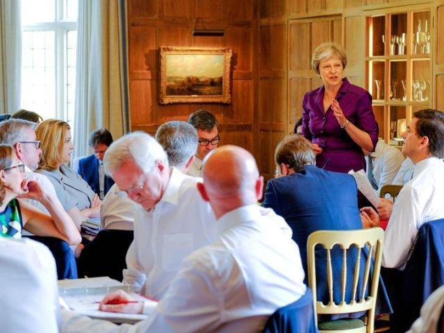 7月6日,英國首相特雷莎·梅(站立者)在首相鄉村官邸契克斯別墅舉行的內閣會議上發表講話。(新華/路透)