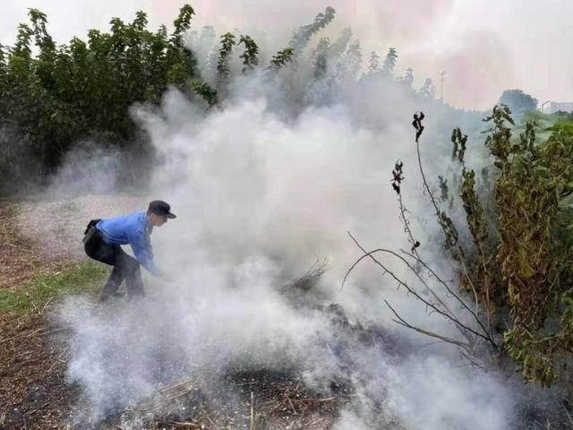 居民露天焚烧垃圾  城管队员紧急灭火
