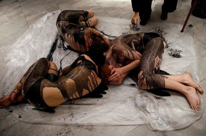 环保主义者为抗议石油公司 涂满黑漆半裸躺地