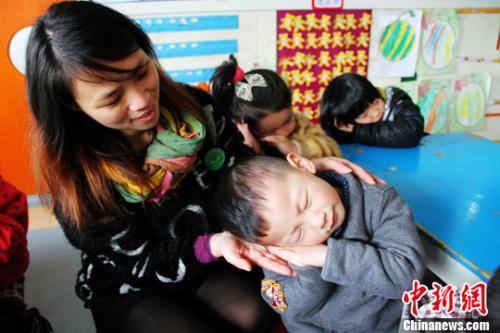 """资料图:图为幼儿园老师正在教儿童学""""睡觉""""。李建平 摄"""