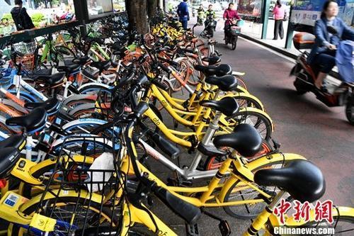 资料图:多个企业的共享单车扎堆停放在城市街头。中新社记者 张斌 摄