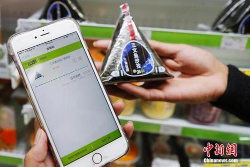 近年,移动支付在中国逐渐流行。图为顾客扫描商品条形码手机自助结账。 殷立勤 摄
